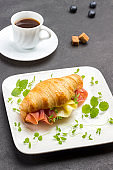 Croissant with jamon and cheese and greens on white plate.
