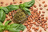 Basil leaves and pine nuts, pesto sauce in glass bowl.