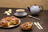 Raisin buns in cardboard plate. Teapot and cup of tea.