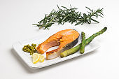 Grilled salmon green peas, lemon sprig of rosemary on white