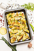 Baked potatoes in baking dish. Rosemary and green peppers, garlic and lemon on table.