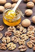 Walnut kernels, whole walnuts, nuts, glass jar with honey.
