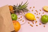 Paper bag with fruit on pink background: apple lemon grapefruit