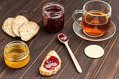 Tea drinking. Jar of honey, sandwiches with jam.