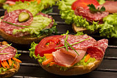 Sandwiches with meat and greens, bun with grains on metal grill.