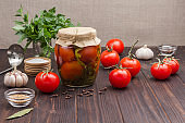Glass jar of canned tomatoes, fresh tomatoes, green parsley, garlic and spices