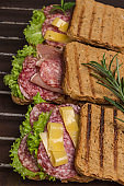 Grilled sandwiches with salami, cheese and salad on metal grill.