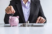 Woman putting coin in pink piggy bank for step up growing business to profit and saving with piggy bank, Saving money for future plan and retirement fund concept
