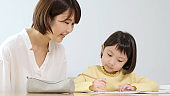 young asian girl studying with mother at home