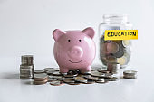 Images of stacking coins pile and pink smiling piggy bank to growing and savings with money box, Saving money for future plan and education fund concept