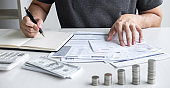 Images of stacking coin pile and Husband using calculator to calculating expenditure receipt bills of various activity cost and expenses in home office and written make report to plan of spent