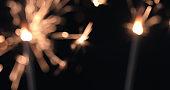 Firework sparkler burning on black