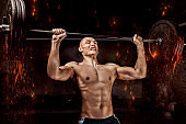 Portrait of an athlete who is lifting the barbell in the gym. The concept of sport and healthy lifestyle.