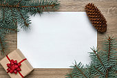 New Year or Christmas festive background. White sheet of paper with copy space, gift box and Christmas tree branches on wood. Flat lay, view from above