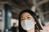 Woman use N95 mask protect smog PM2.5 dust and Coronavirus in city stock photo