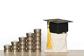 Graduation hat on the bag with Stack of coins money on white background, Saving money for education concept