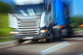 Truck in a blur on the road in motion. The danger of a collision or emergency situation. Violation of rules by truckers
