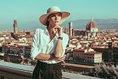 Portrait of a charming girl standing in a square in Florence. View of Santa Maria del Fiore. Tourism concept. Italy.