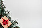 Christmas or New Year's composition with a gift box and Christmas tree branches on white background. Copy space, flat lay, view from above