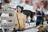 Asian woman looking for shell hanging mobile for her home decloration at Chatuchak market