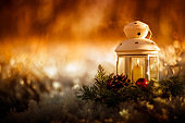 festive christmas card candle it burns in an elegant spruce wreath stands in the new year's garden among the snow