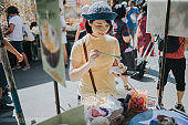 Thai tourist buying coconut ice cream at  Chatuchak Weekend Market