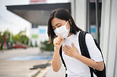 Asian woman wearing protective face mask coughing and standing department store. New lifestyle with Corona Virus COVID-19.