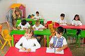 School kids studying in classroom with teacher