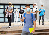 Teenager in protective mask going to school in autumn