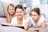 Woman reading book to daughters on sofa
