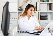 Female doctor working on laptop in office