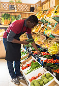 Seller arranging vegetables and fruits on counter