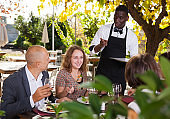 Waiter serving meals to friendly company at open-air restaurant