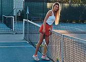 Sportive woman is playing tennis at court