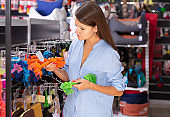 Young woman customer is looking new toys for dog