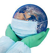 Pandemic concept - doctor's hands in gloves holding the planet Earth in a medical mask (Eastern hemisphere)