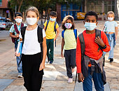Tween boys and girls in protective masks going to school lessons