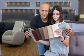 Couple holding samples of upholstery fabric