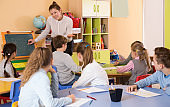 Group of pupil listening cheerful teacher