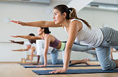 Young woman practicing yoga at group class
