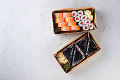 Tasty sushi rolls in disposable kraft paper boxes, sauces, chopsticks.  Sushi for take away or delivery