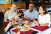 Positive people enjoying pizza and wine in cozy restaurant