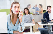 Upset young woman foreground in busy open plan office