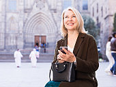 Business woman dialing message on mobile phone sitting on a street bench