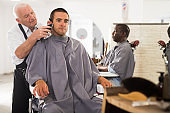 Man getting haircut from aged barber
