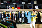 Adult woman shopping clothes in men store