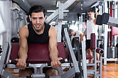Guy training on fitness machine in gym