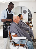 African barber putting on hairdresser cape to elderly client