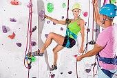 Couple of alpinist practicing in pair indoor rock-climbing