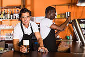 Bartender offering glass of beer, man pouring beer on background